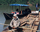 Loggers rafting cut logs of highly valued mahogany trees, Peru.