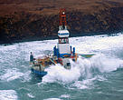 Waves crash over the conical drilling unit Kulluk where it sits aground on the southeast side of Sitkalidak Island, Alaska
