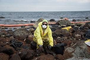 A WWF-Norway staff member assists in the clean-up after an oil spill off the coast of Langesund, Norway in July 2009.