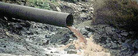 Sewage pipe spewing pollution from a factory directly into a river near Mumbai (Bombay). India. rel=