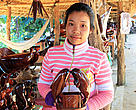 Khoeun Sitha sells wooden dolphin sculptures at her stand in Kampi.