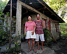 A fisherman and his wife standing in front of the concrete house they built from tuna fishing earnings. Albay, Philippines.