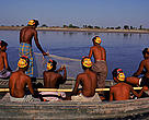 Fishermen wearing masks to protect from tiger (<i>Panthera tigris</i>) attack. Tigers attack by biting back of neck, mask with prominent eyes intended to mislead and prevent tiger from attacking from rear. Sunderband, W Bengal, India.