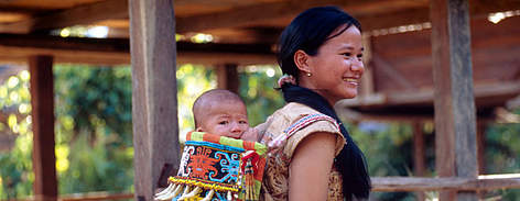 A Kenyah Dayak mother carrying her baby in a traditional hand made carrier. Long Alango village, ... rel=