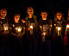 A group of people holding candles wearing Earth Hour shirts celebrating Earth Hour 2010 outside against a dark sky, Canada.
