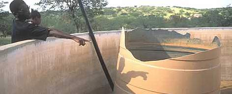 Bob Guibeb of the Khoadi Hoas Conservancy surveys damage to a container that collects rainwater for ... rel=