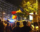 A protester waives the Romanian flag at a protest march to save Rosia Montana from a gold mine project
