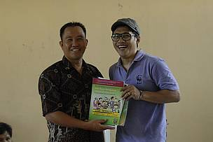 Nugie symbolically hands over the book to schools in the Heart of Borneo