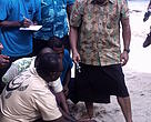 Turtle monitor Pita Qarau (with turtle) explains the intricacies of tagging to Fiji Prime Minister Voreqe Bainimarama on Yadua Island in Bua province