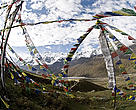 Buddihst prayer flags fluttering in the wind with snow capped mountain in the background. Kanjin Gompa, Langtang National Park, Nepal.