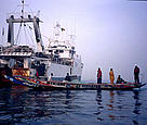  A large Spnaish trawler floats in stark contrast to the local fishermen's boat, Senegal. / &copy;: WWF-Canon / Jo Benn