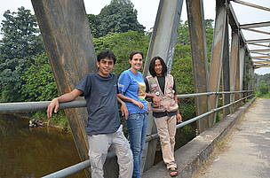 Three WWF team members standing on a bridge