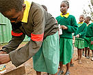School girls filling water bottles at a water tap. Water is a threatened resource and with population growth and expanding urbanization the pressure can only increase. Protecting forests around water catchment areas is no longer a luxury but a necessity.  Nairobi City, Kenya