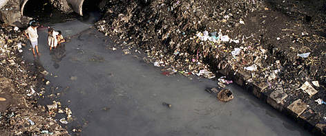 Children playing in heavily polluted river in the slums near Bombay, India. rel=