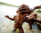 Bathing a young child in the April River, Pukapuki village.